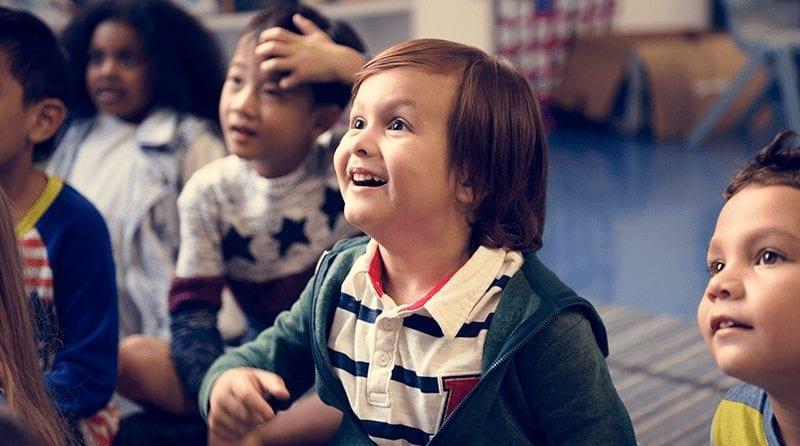 children sitting on the floor in nursery looking up in awe