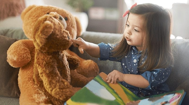 little girl in blue dress reading a book to her brown teddy bear