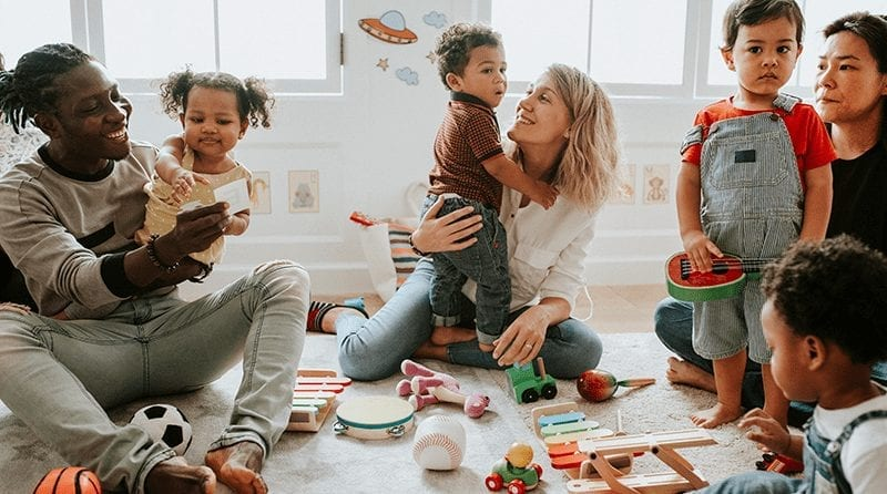 diverse parents and children sitting on the floor in a play room
