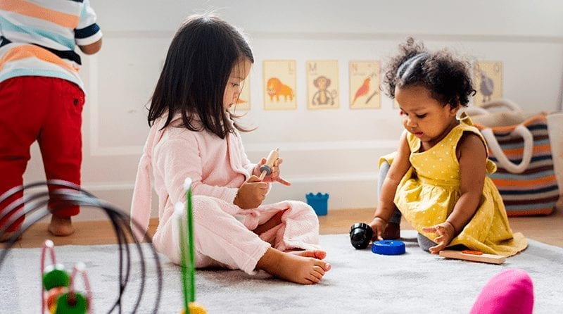 Two toddlers playing with toys in a nursery room