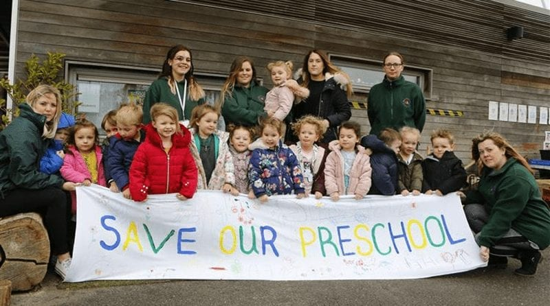 teachers and pupils at Harrietsham preschool standing outside of the building holding a banner 'save our preschool'