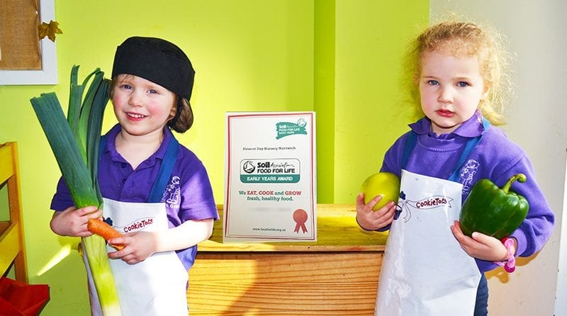 Two children at Nantwich nursery holding vegetables in their hands