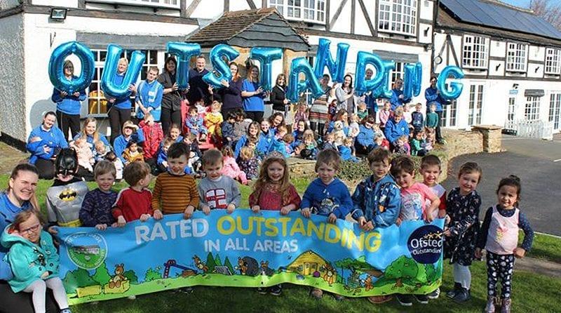 preschool children and staff standing outside their preschool with balloons saying 'outstanding'