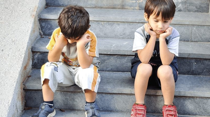 two sad boys sitting on stairs. Both are holding their heads in their hands