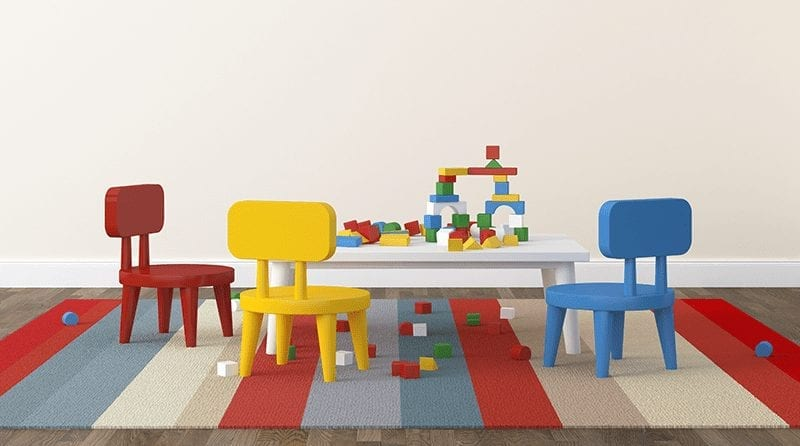 white table with colourful chairs and wooden building blocks on top of it