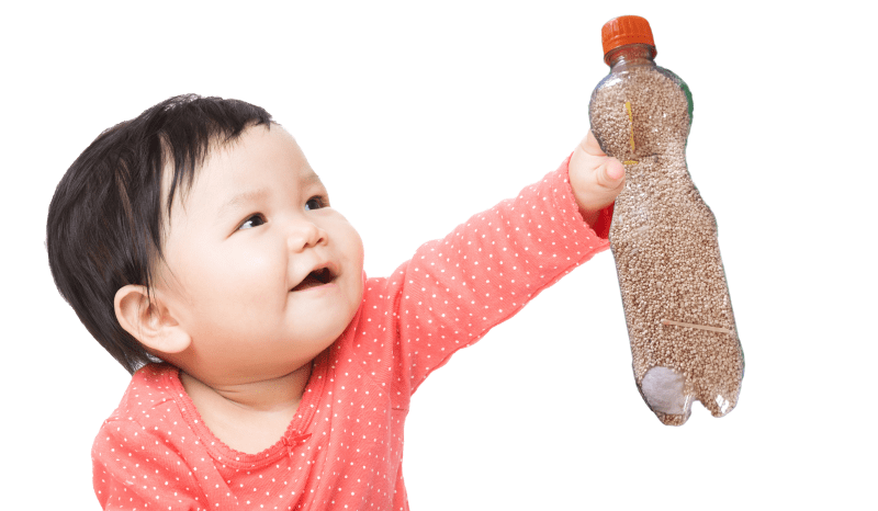 toddler stretching hand and holding a bottle filled with grain