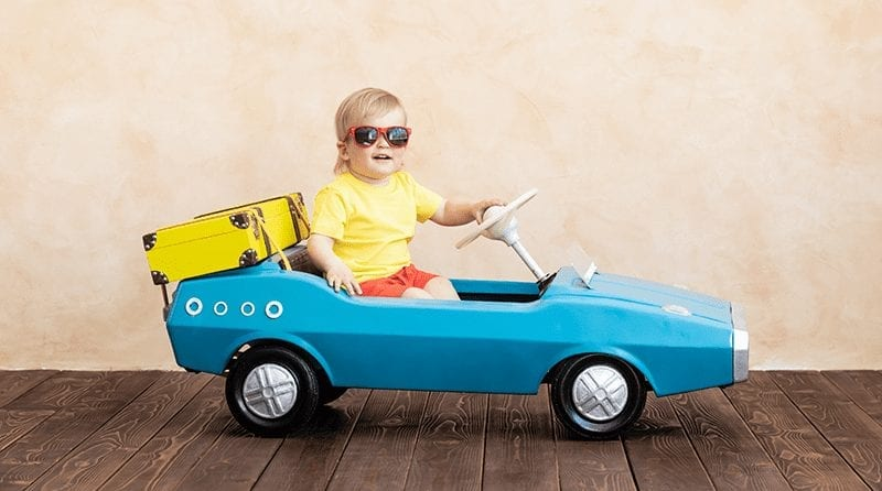 Cool looking little boy in shades sits in a toy vintage car with suitcase packed tied to the back of the car