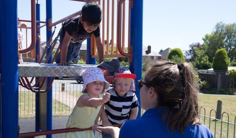 nursery worker talking to three children in the playground