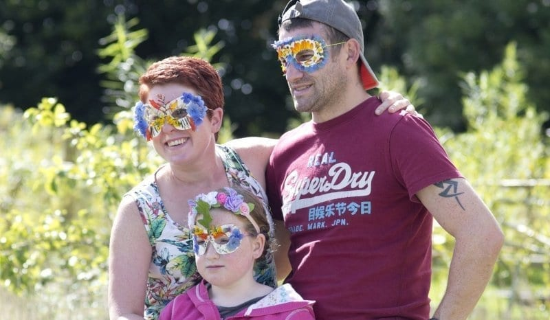 mother, father and a daughter wearing floral eye masks outside