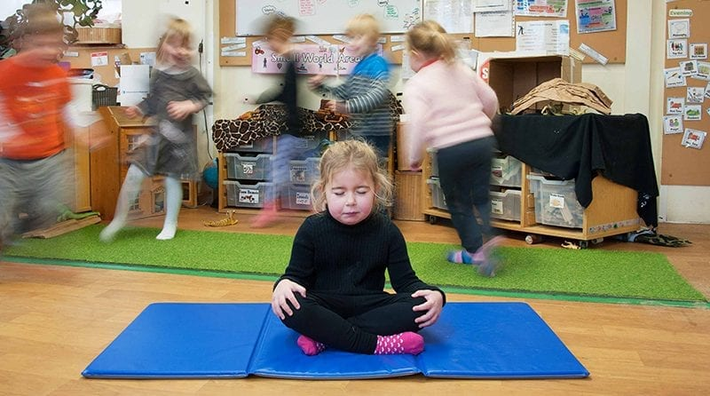 Local nursery introduces yoga sessions into curriculum, Little girl on a yoga mat, doing yoga in the middle of a bustling nursery