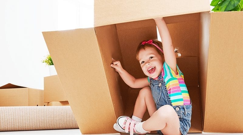 little girl playing with a cardboard box