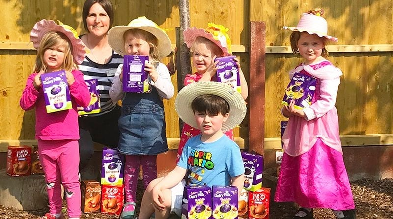 Group of children with their donated Easter eggs in the garden, with Nursery Manager, Nicky Cunningham