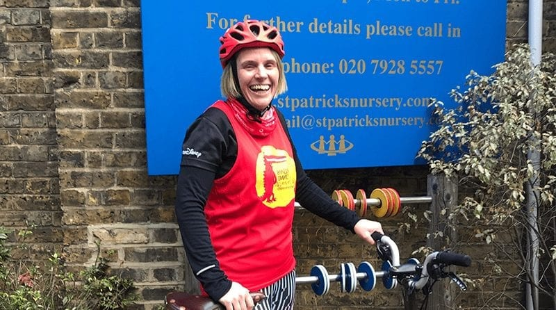 Nursery manager Lynnsey Fitzgerald stands in cycle gear with her bike, proudly in front on the nursery sign