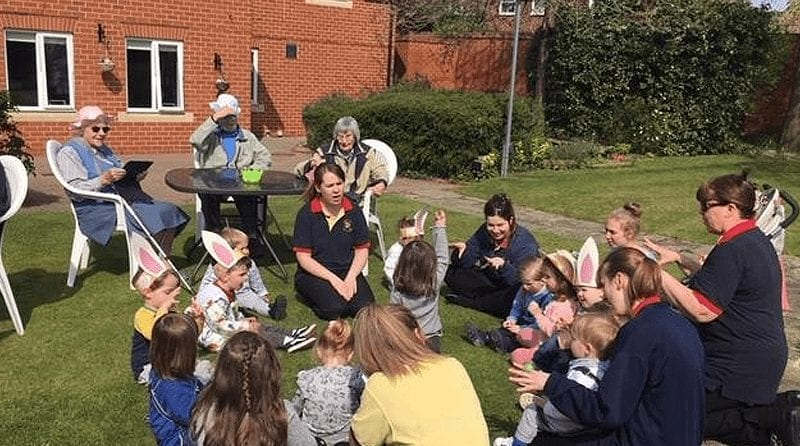 Nursery toddlers and elderly residents from Abbeyfield gathering outside ready to take part in Easter egg hunt