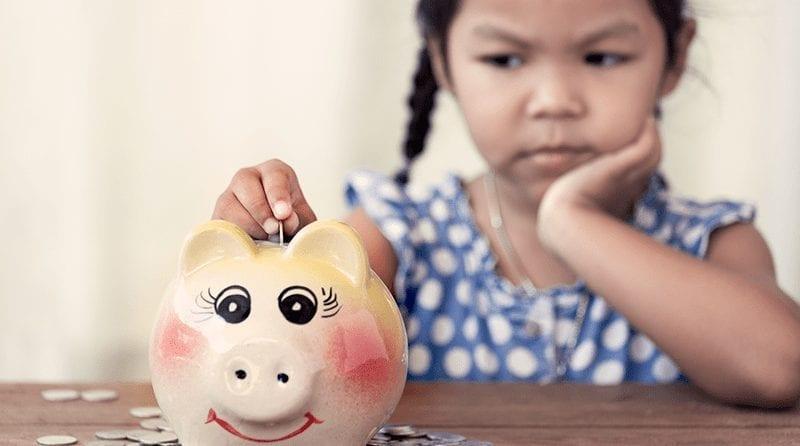 Little girl putting money in her piggy bank. She looks upsaet