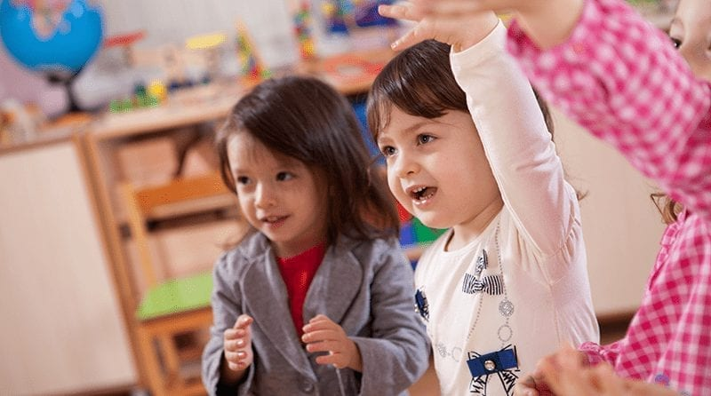 two toddlers playing in nursery. One is raising hand