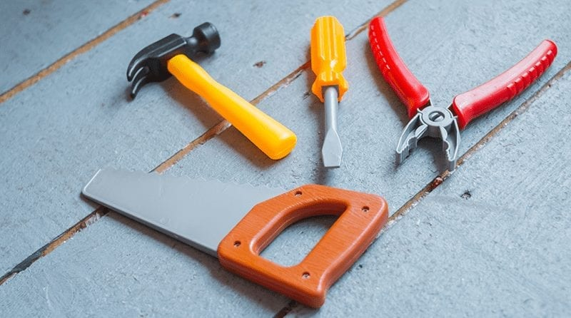 Children's toy work tools: saw, hammer, screwdriver and pliers on a wooden background
