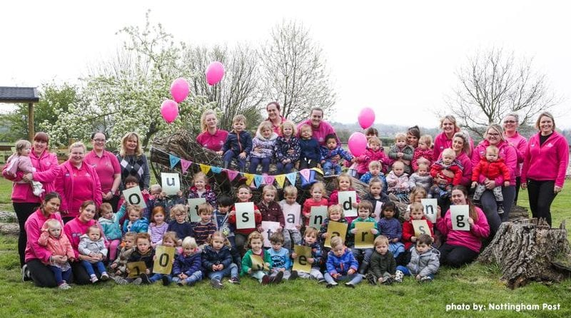 """Large group photo of nursery children and staff, gathered outside with balloons and bunting, celebrating their """"outstanding"""" rating from Ofsted"""