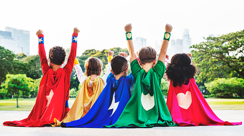 5 young children dressed in colourful superhero costumes out in the park