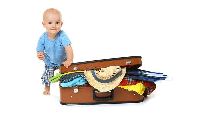 Little toddler boy posing by a packed suitcase spilling out the edges