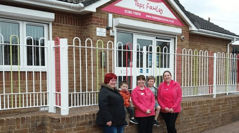 "Staff members and a child pose outside the building, signage stating ""Tops Fawley"""