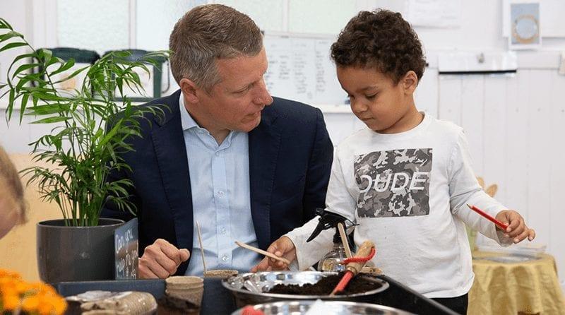 MP Luke Pollard sits talking to a young pre-school boy