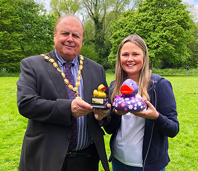 Elmscot Day Nursery and Nursery School manager, Leann Banks, stands with Nantwich town mayor Darren Marren, holding the winning duck - elmsquack -  and the prize golden duck