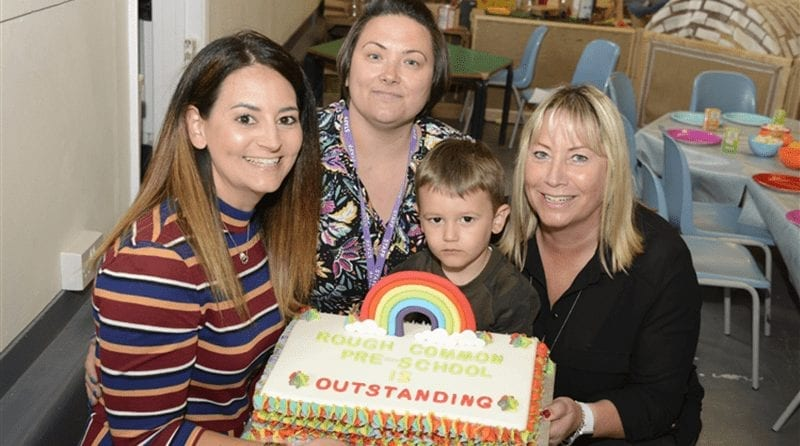 "3 adults and a little boy posing with a celebratory cake bearing the word ""outstanding"""