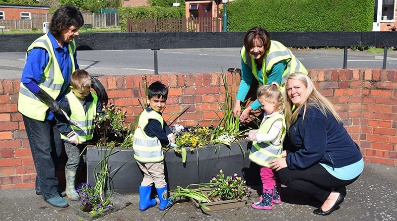 Little toddlers helping 'Studley in Bloom' brighten up the community by planting flowers