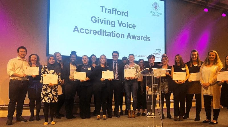 Group of proud happy people stand on stage to collect their award at the Trafford Early Years Giving Voice award ceremony