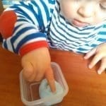 Little boy playing with slime at the table