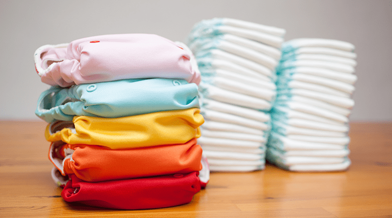 Stack of eco-friendly nappies and a stack of disposable nappies