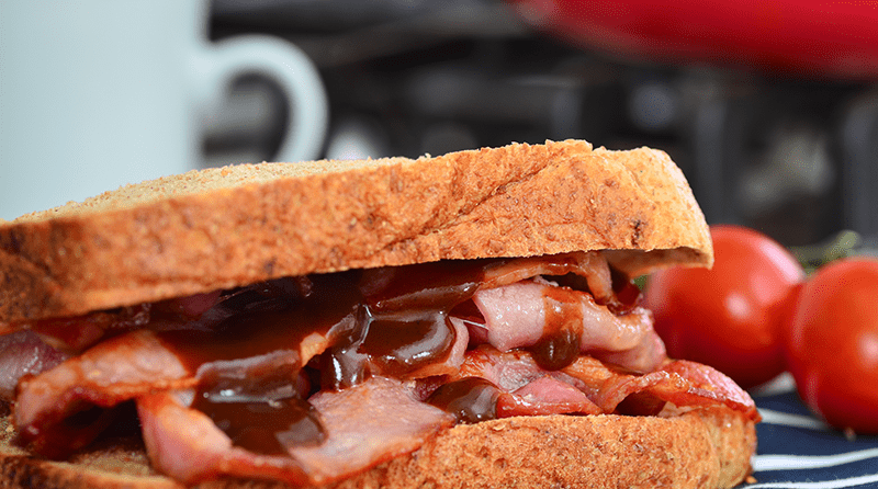 Close up of a crispy bacon sandwich with brown sauce