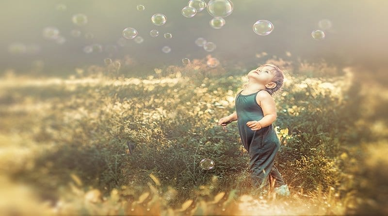 cute baby playing with soap bubbles